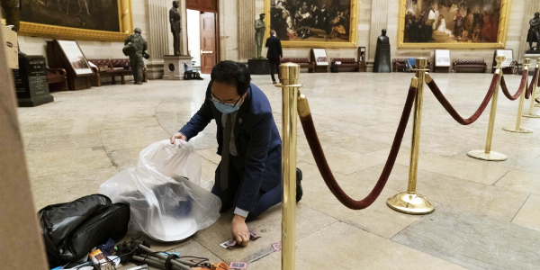Photo: Rep. Andy Kim, D-N.J., cleans up debris and personal belongings strewn across the floor of the Rotunda in the early morning hours on Jan. 7, 2021, after a mob stormed the Capitol.
